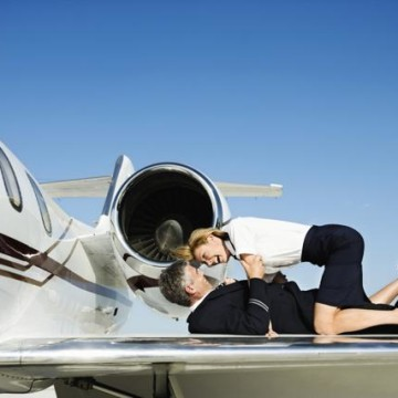 Stewardess and Pilot Embracing on Airplane Wing