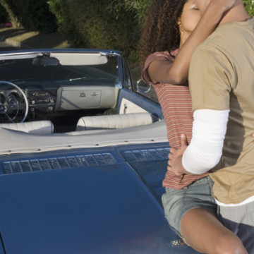 Young Couple Macking on Car Trunk --- Image by © Heide Benser/Corbis