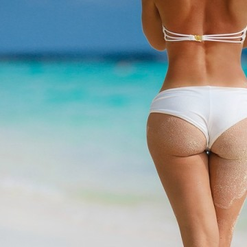 The beautiful figure of the woman, the rear view, in white bikini, buttocks in sand, costs on a sandy beach on the bank of the blue ocean, having crossed feet.